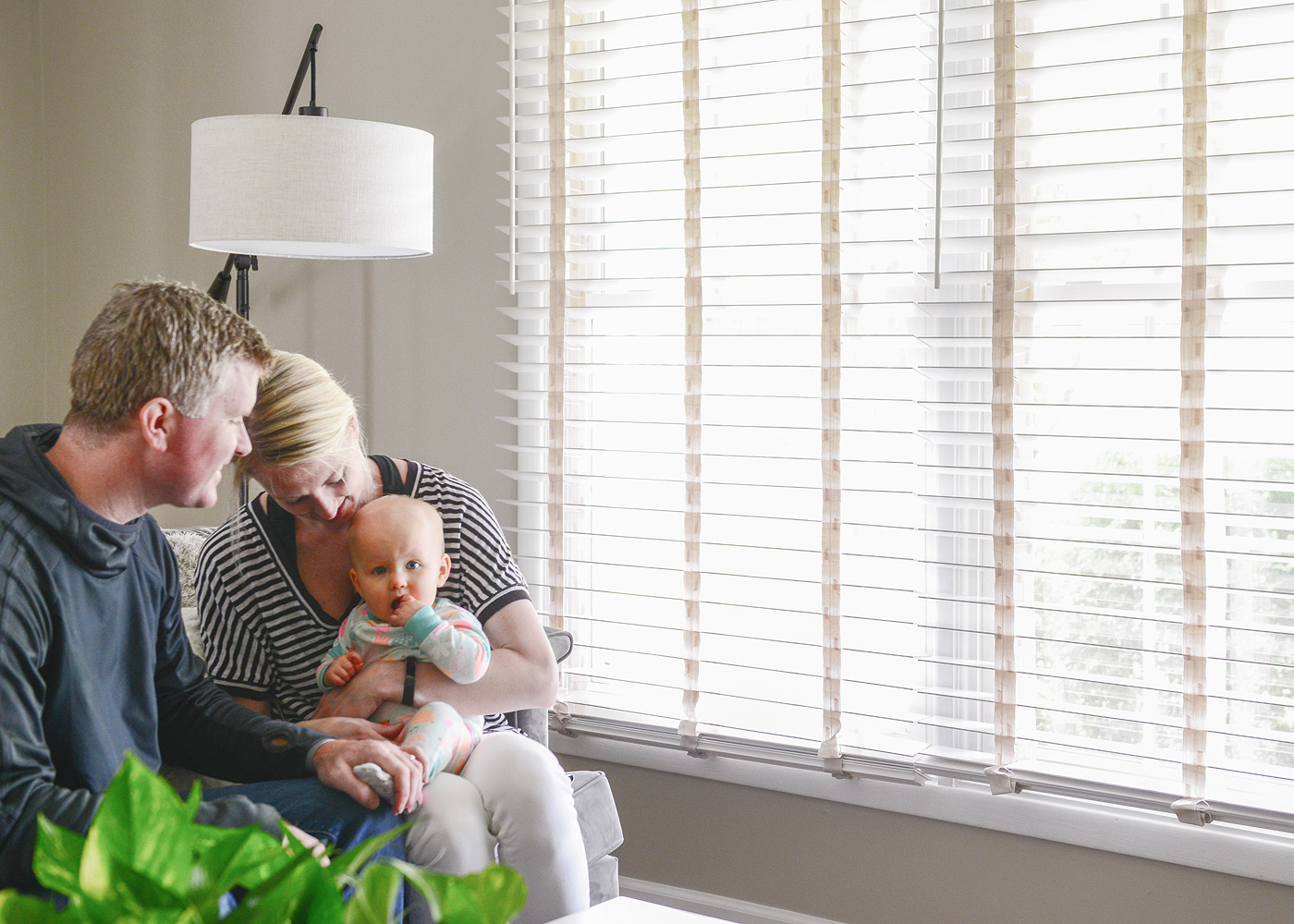 Family in living room with wood blinds